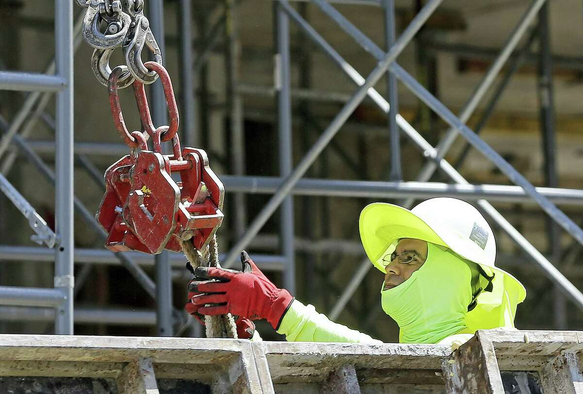 A construction worker continues work on a condominium project in Coral Gables, Fla. On Friday the Labor Department will release the U.S. jobs report for June.
