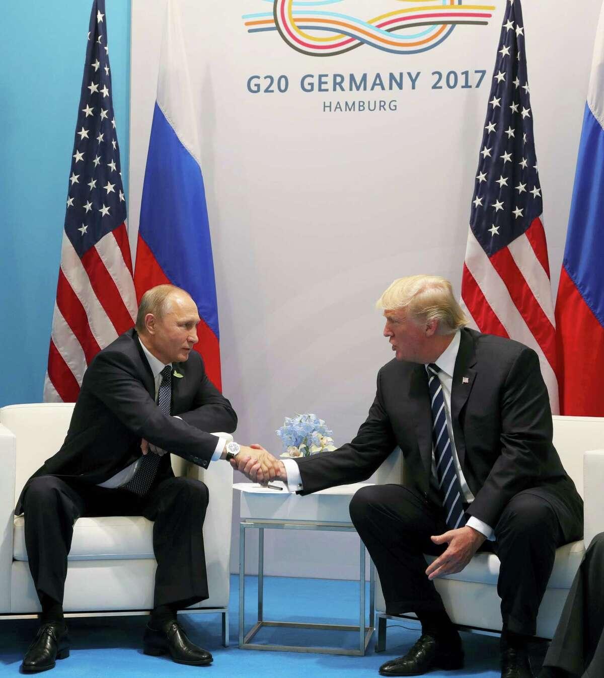 U.S. President Donald Trump, right, and Russian President Vladimir Putin shake handsduring the G20 summit in Hamburg Germany, Friday July 7, 2017.