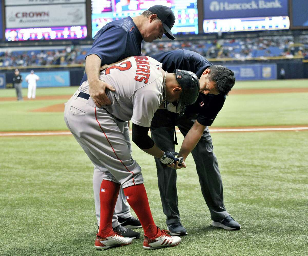 Boston Red Sox manager John Farrell, left and assistant athletic trainer Masai Takahashi, right, check on Xander Bogaerts after he was hit by a pitch.