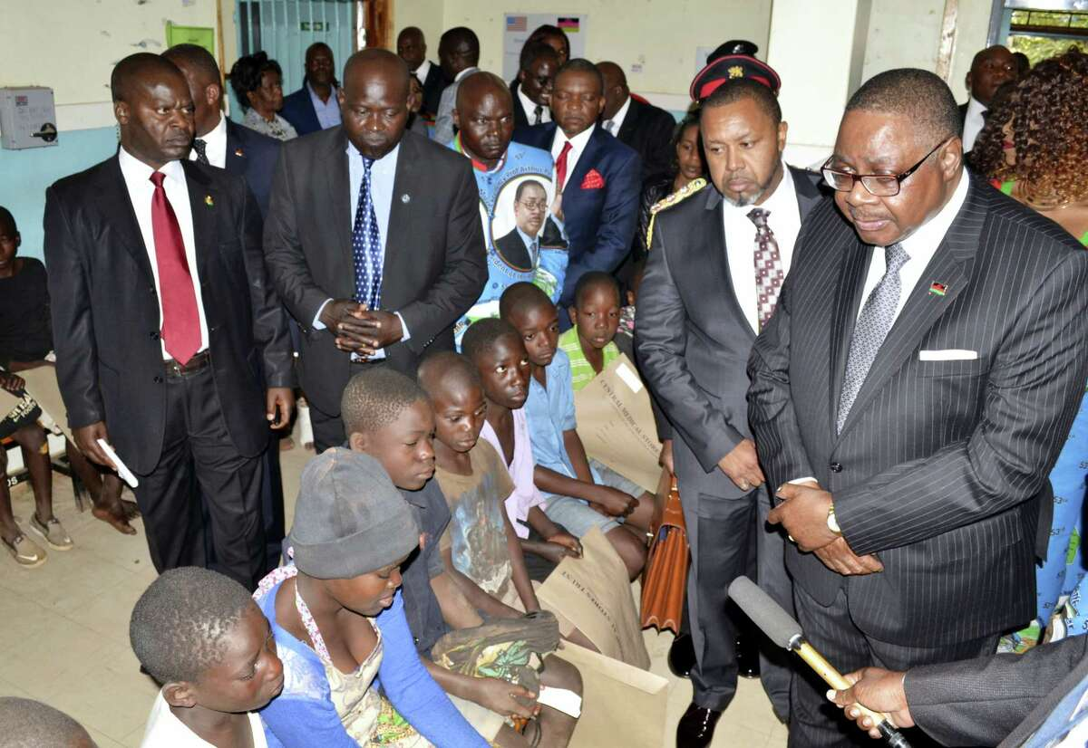 Malawian President Peter Mutharika, right, visits injured children in Lilongwe, Malawi, Thursday, July 6, 2017. A crowd stampeded at the Bingu National Stadium during Independence Day celebrations, killing 8 people and injuring more. Most of the victims were children .
