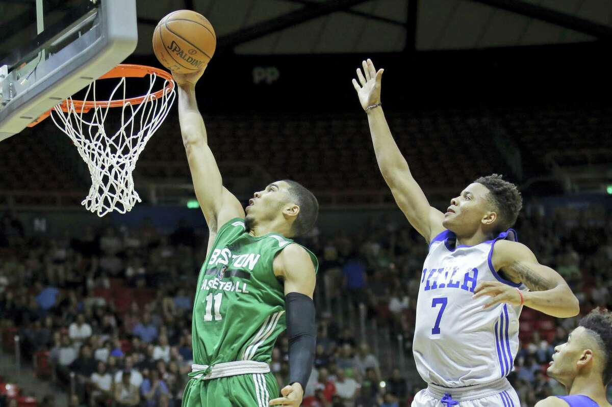 Boston Celtics forward Jayson Tatum (11) lays the ball in as Philadelphia 76ers guard Markelle Fultz (7) defends during the second half of an NBA summer league basketball game Monday, July 3, 2017 in Salt Lake City.