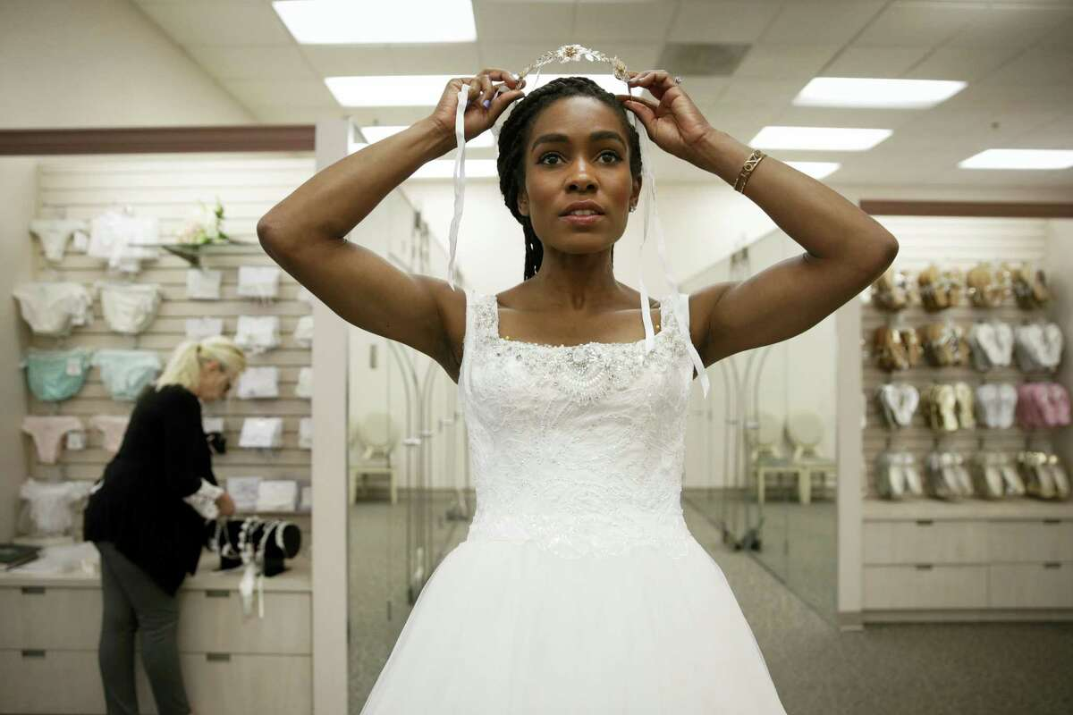 """Shevon Stoddart, a 34-year-old Jamaican hurdler, tries on a tiara while getting her wedding dress fitted ahead of her July wedding with two-time Olympic high jumper Jamie Nieto, who is recovering from a spinal cord injury after a mistimed backflip on June 6, 2017 in Burbank, Calif. """"The wedding will be an amazing day for us, and our family and friends and supporters who've helped us get through this,"""" said Stoddart."""