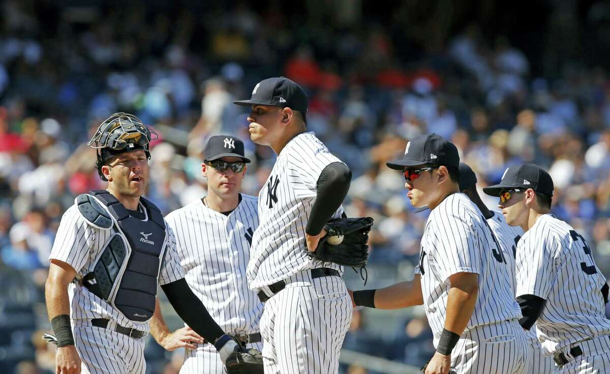 New York Yankees relief pitcher Dellin Betances, center, stands on the mound after walking in the go-ahead run in the eighth inning against the Toronto Blue Jays Wednesday. Yankees manager Joe Girardi took Betances out of the game after the run.
