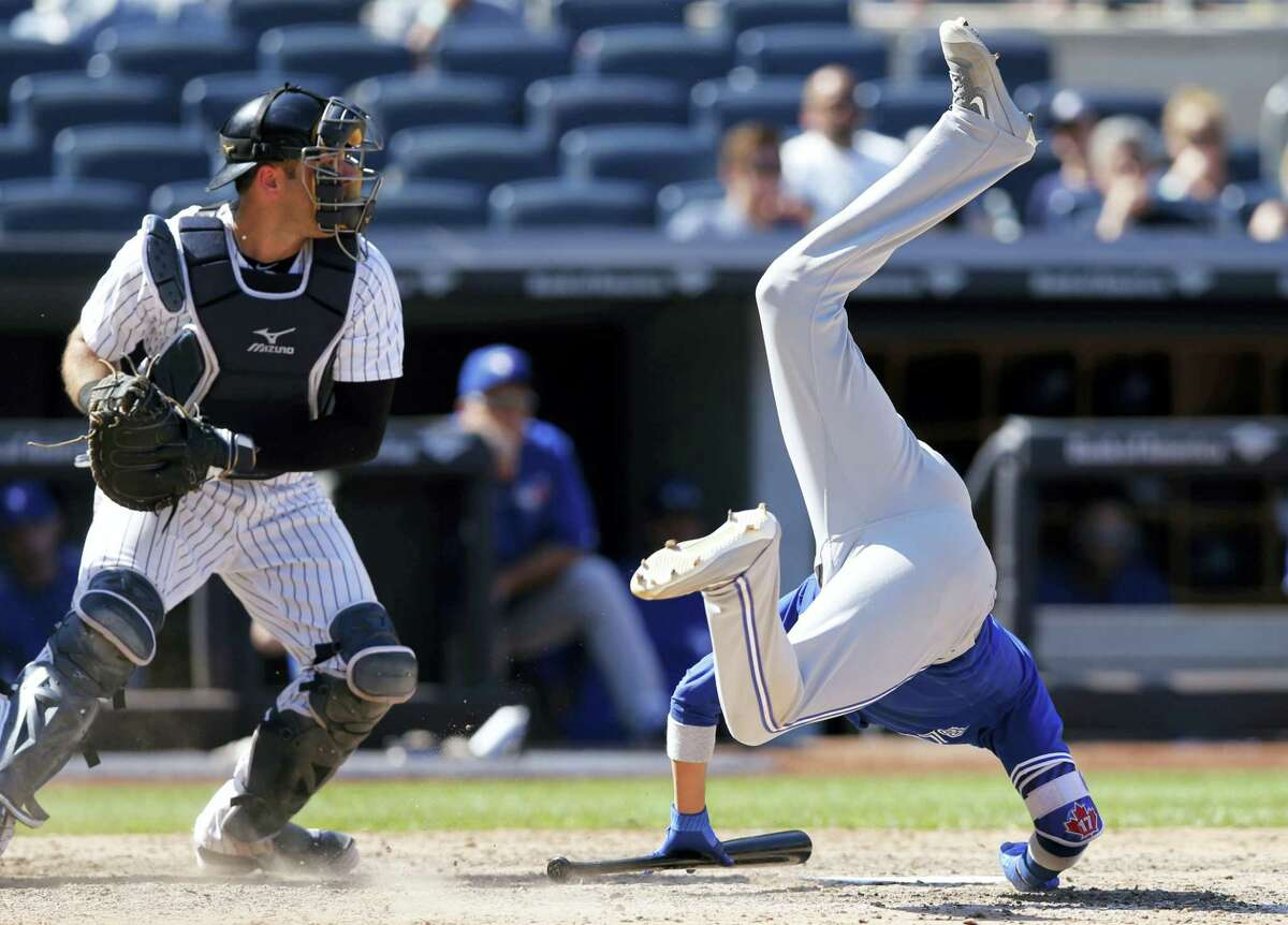 Toronto Blue Jays' Ryan Goins flips after avoiding Dellin Betances's eighth-inning pitch. Yankees catcher Austin Romine prepares to throw the ball back to Betances.