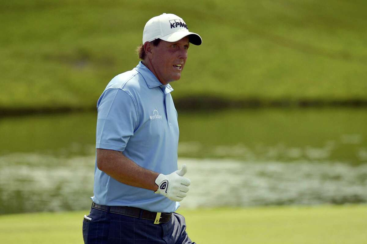 """Phil Mickelson gestures to fans on the 18th hole during the final round of the St. Jude Classic golf tournament earlier this month. Mickelson will have brother Tim on his bag starting today at the Greenbrier Classic in his first tournament since parting ways with his caddie of 25 years, Jim """"Bones"""" Mackay."""