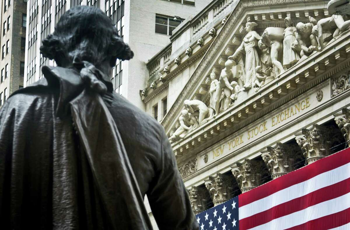 A statue of George Washington stands at Federal Hall near the flag-covered pillars of the New York Stock Exchange.
