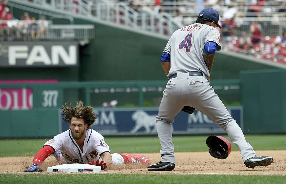 Washington Nationals' Bryce Harper, left, slides into third during the fifth inning of a baseball game against New York Mets third baseman Wilmer Flores Tuesday, in Washington. Harper hit a single and went to third on a fielding error by the Mets' Jay Bruce.