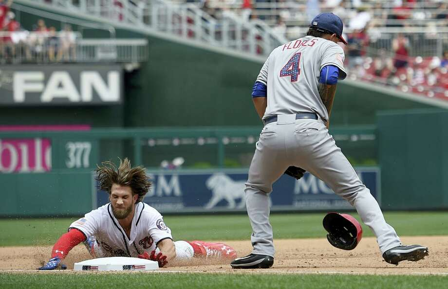 Washington Nationals' Bryce Harper, left, slides into third during the fifth inning of a baseball game against New York Mets third baseman Wilmer Flores Tuesday, in Washington. Harper hit a single and went to third on a fielding error by the Mets' Jay Bruce. Photo: NICK WASS - THE ASSOCIATED PRESS  / FR67404 AP