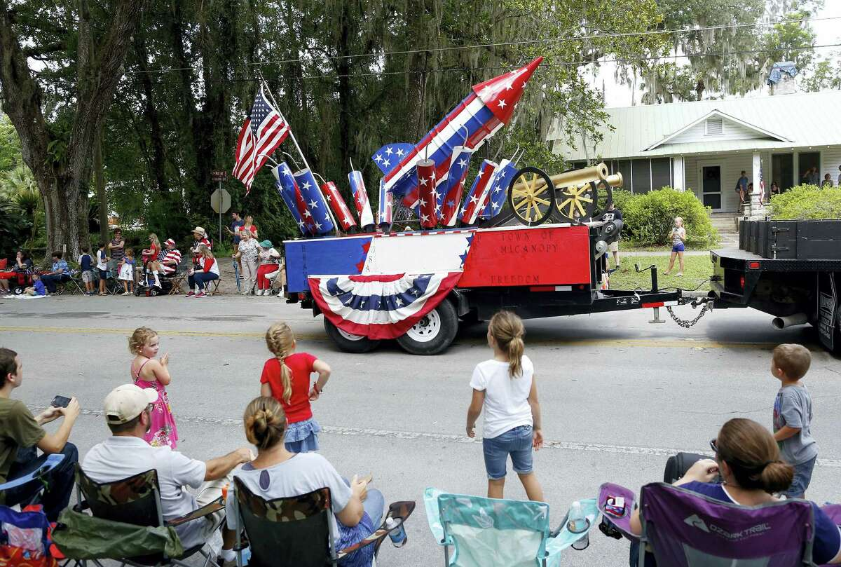 A float loaded with a rocket, cannons, and firecrackers is pulled down Tuscawilla Road during the annual Fourth of July Parade, in Micanopy, Fla., Tuesday, July 4, 2017.