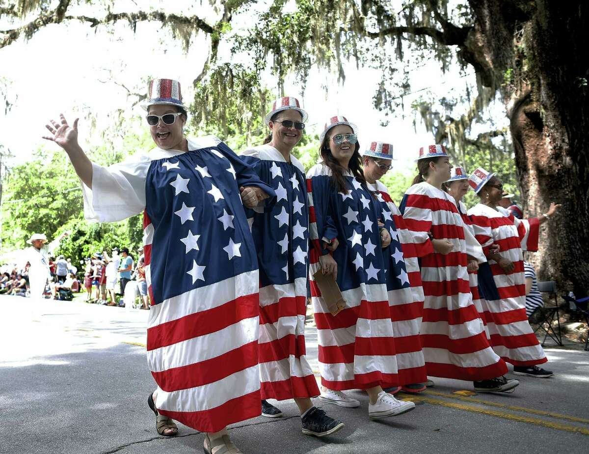 Brad McClenny/The Gainesville Sun via AP Ladies dressed in outfits that make a large American flag walk down Tuscawilla Road during the annual Fourth of July parade, in Micanopy Fla., Tuesday July 4, 2017.