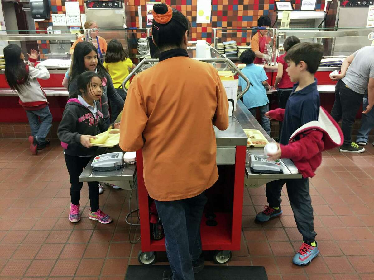 In this Thursday, May 4, 2017 photo, second grade students Angelina Lopez, left, and Nasim Hamdouni, right, enter a student account code to track lunch purchases at Gonzales Community School in Santa Fe, N.M. All students are offered the same lunch at Gonzales and other Santa Fe public schools to avoid any chance of embarrassing students whose parents may have fallen behind on meal payments. New Mexico in April became the first state to outlaw the shaming of children for any unpaid meals.