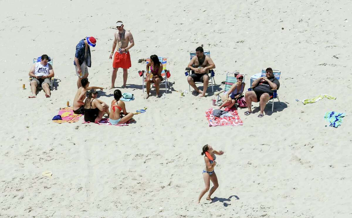 """In this Sunday photo, New Jersey Gov. Chris Christie, right, uses the beach with his family and friends at the governor's summer house at Island Beach State Park in New Jersey. Christie is defending his use of the beach, closed to the public during New Jersey's government shutdown, saying he had previously announced his vacation plans and the media had simply """"caught a politician keeping his word."""""""