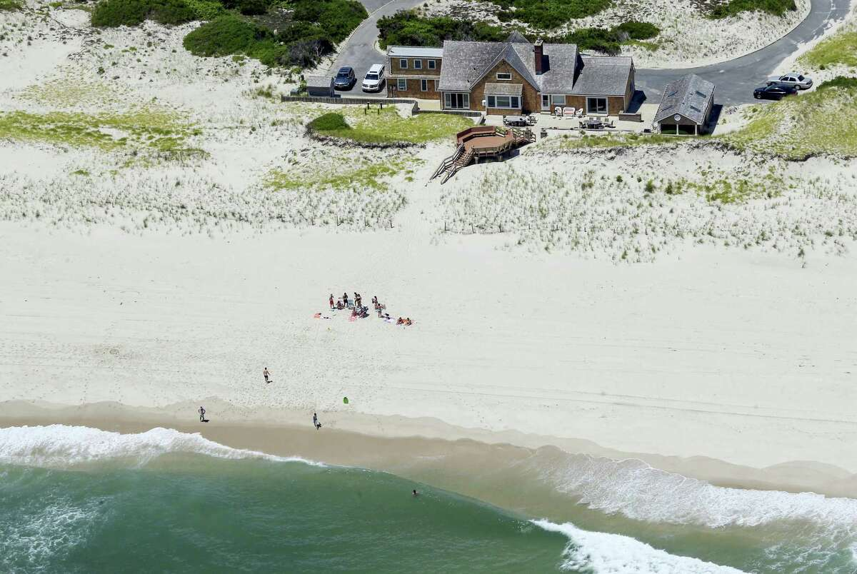 """In this Sunday photo, New Jersey Gov. Chris Christie uses the beach with his family and friends at the governor's summer house at Island Beach State Park in New Jersey. Christie is defending his use of the beach, closed to the public during New Jersey's government shutdown, saying he had previously announced his vacation plans and the media had simply """"caught a politician keeping his word."""""""