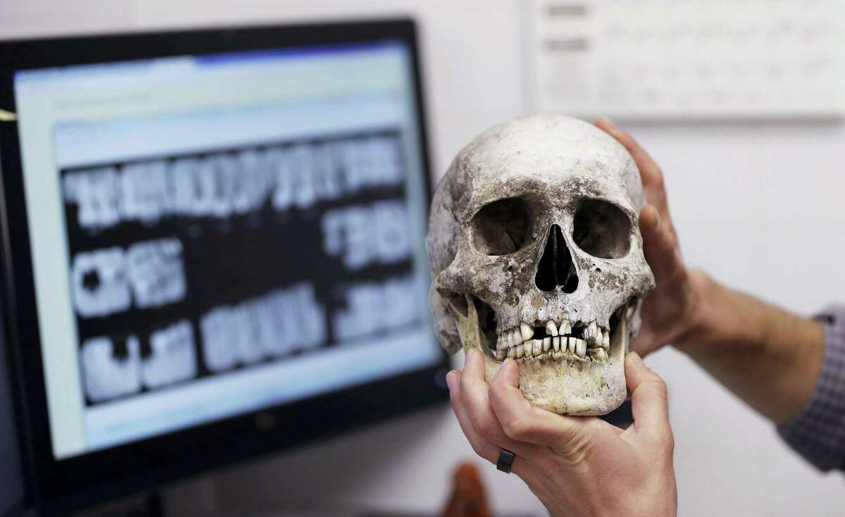 In this Wednesday photo, Dr. Tim Gocha uses dental records as he works to help identify the remains of immigrant who died along the U.S-Mexico border, at the Forensic Anthropology Center at Texas State, in San Marcos, Texas. Forensic investigators and advocacy groups said efforts to identify the remains of immigrants found along the Texas-Mexico border remain slow because DNA comparisons aren't being made with a large pool of potential family members. DNA extracted from immigrants' remains in Texas ends up in an FBI database.