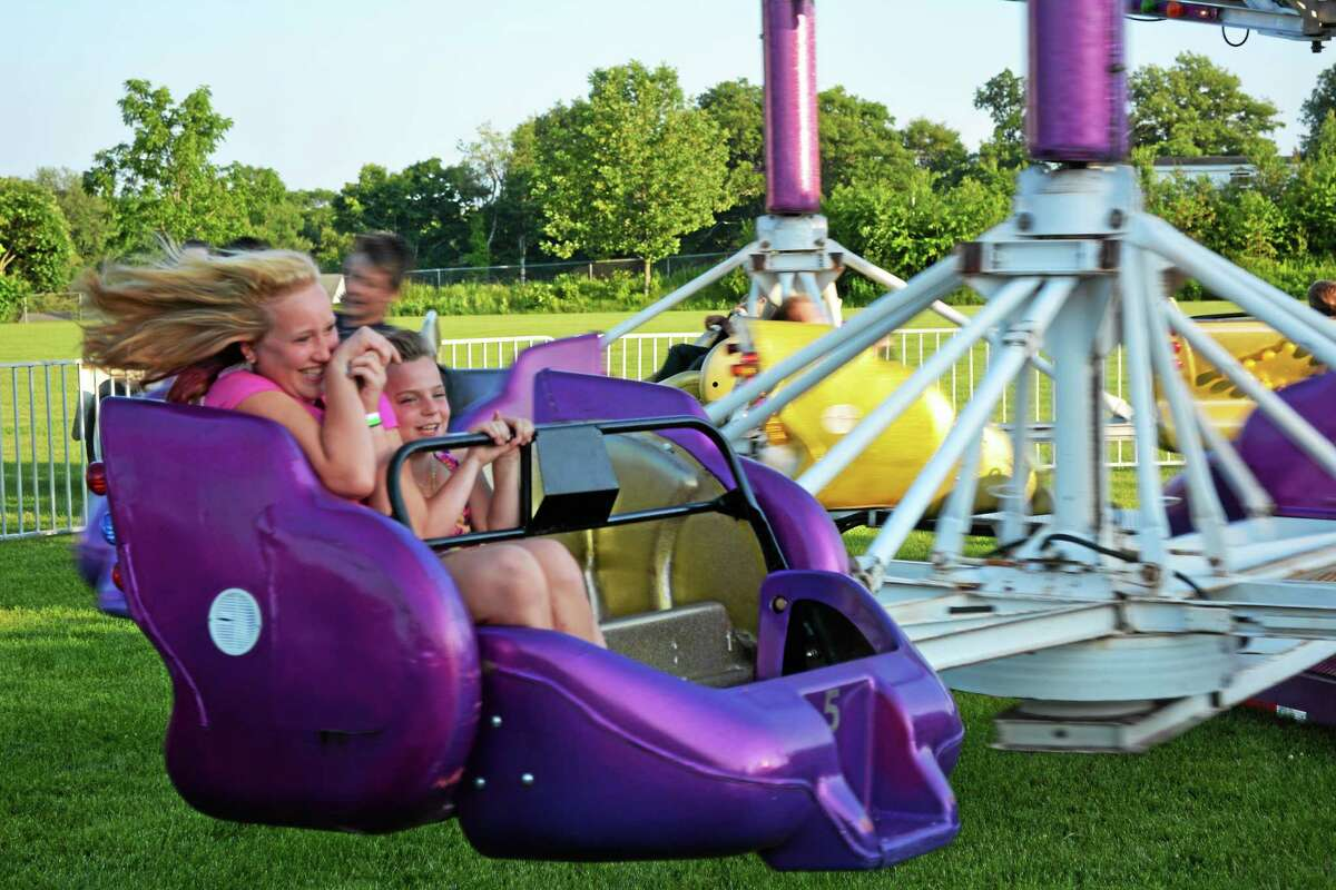 Residents are welcome to attend this year's Independence Day celebration, set for Friday and Saturday at Torrington Middle School. Fireworks are scheduled for Friday night with a rain date of Saturday night. Above, a pair of carnival guests enjoy a ride at last year's event.
