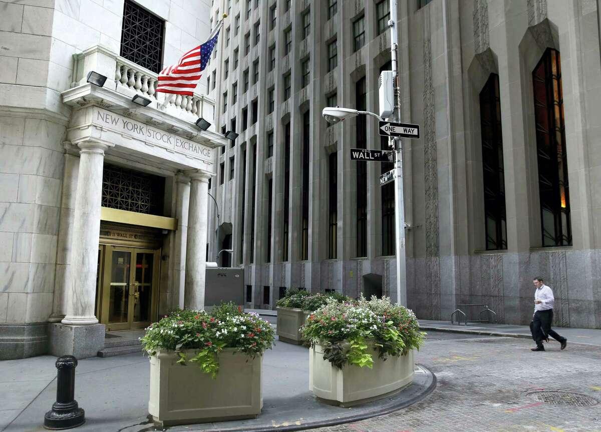 A man walks towards the New York Stock Exchange.