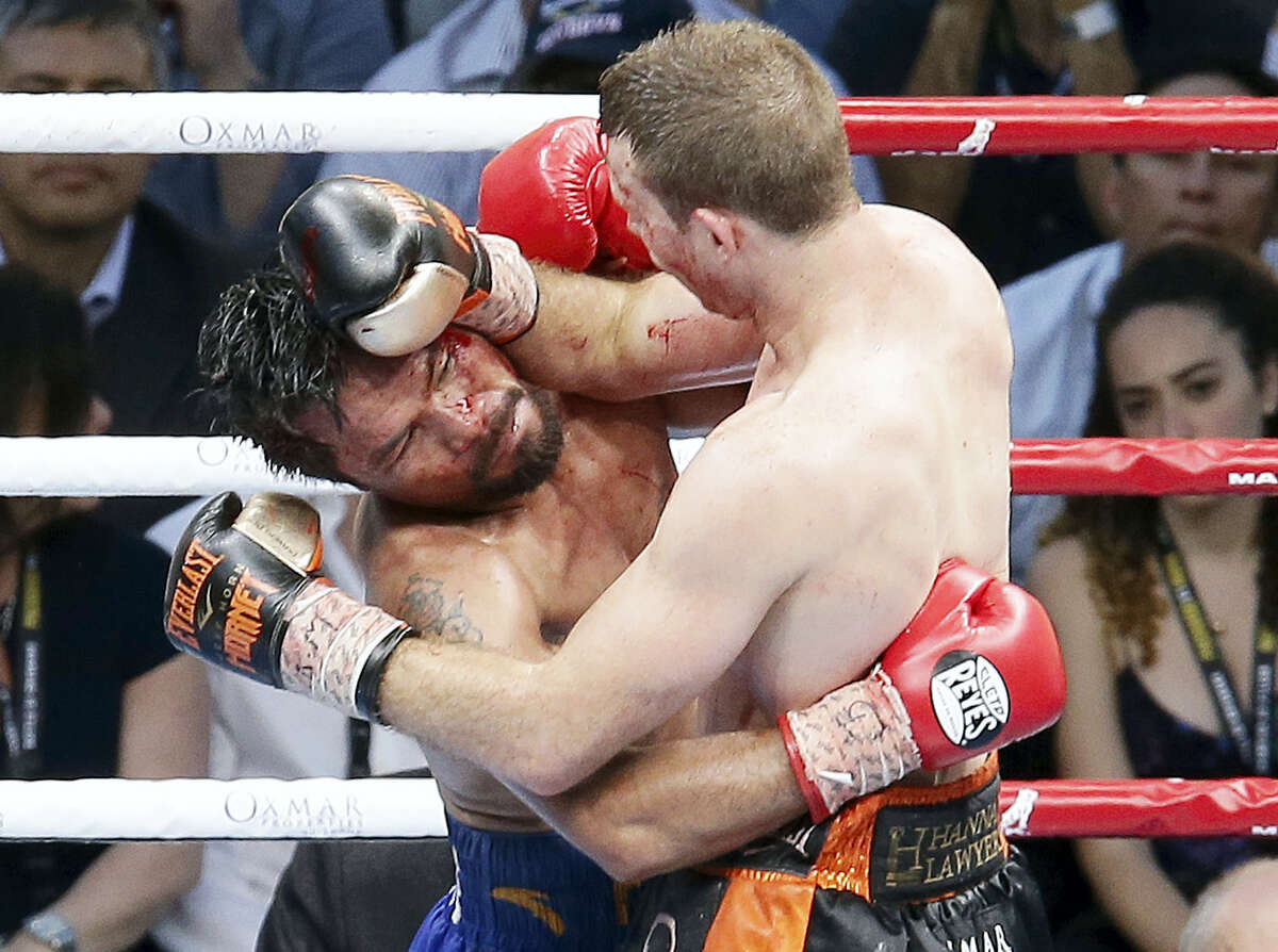 Manny Pacquiao of the Philippines, left, clinches with Jeff Horn of Australia, during their WBO World Welterweight title fight in Brisbane, Australia on July 2, 2017. Pacquiao lost his WBO welterweight world title to Jeff Horn in a stunning, unanimous points decision in a Sunday afternoon bout billed as the Battle of Brisbane in front of more than 50,000 people.