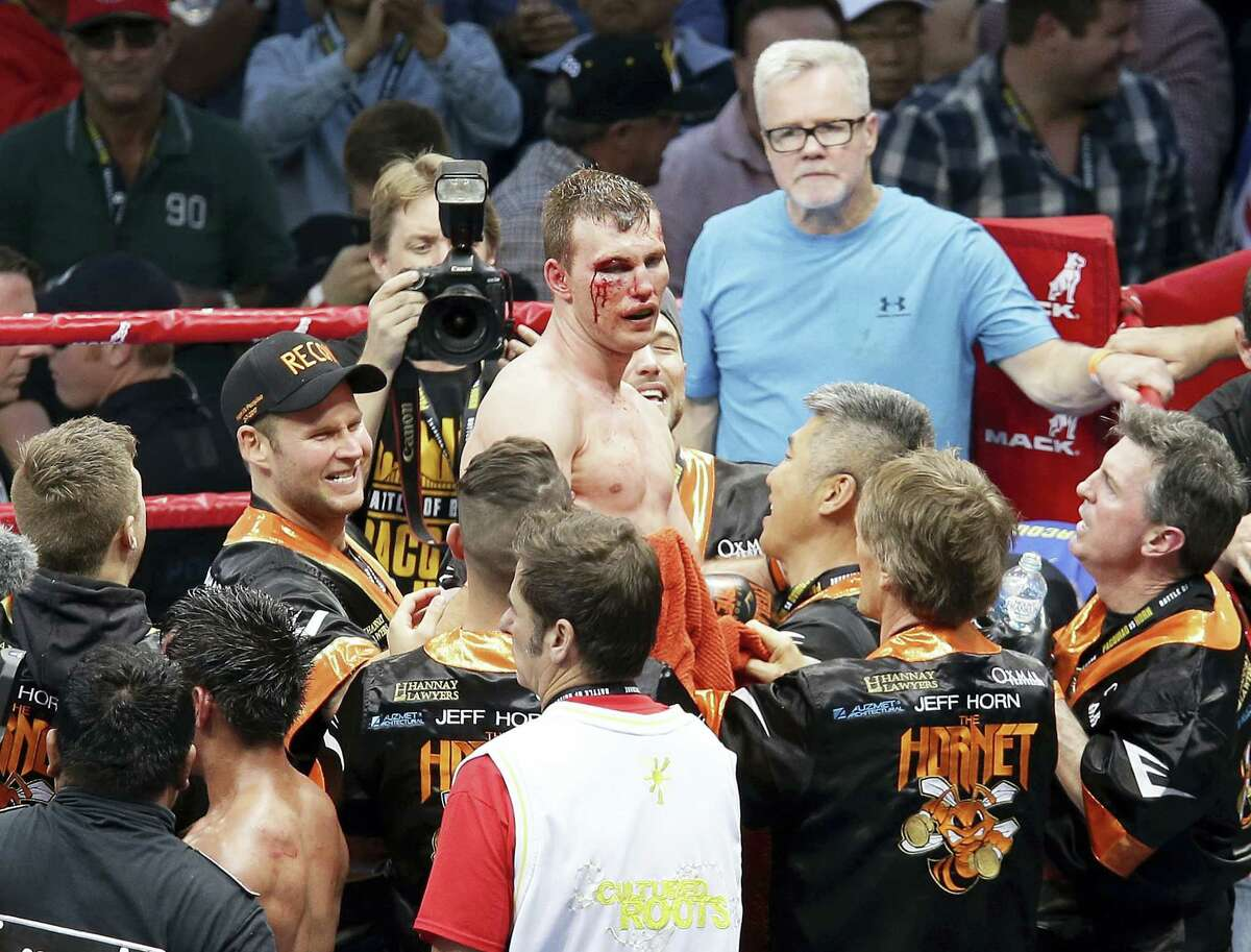 Jeff Horn, top center, of Australia celebrates after beating Manny Pacquiao, bottom second left, of the Philippines, during their WBO World welterweight title bout in Brisbane, Australia on July 2, 2017. Pacquiao lost his WBO welterweight world title to Horn in a stunning, unanimous points decision in the Sunday afternoon bout billed as the Battle of Brisbane in front of more than 50,000 people.