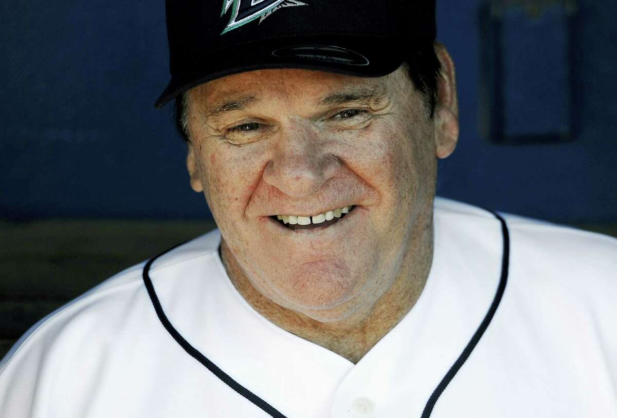 Pete Rose smiles while sitting in the dugout at The Ballpark at Harbor Yard, Monday, June 16, 2014, in Bridgeport, Conn. Rose, banned from Major League Baseball, returned to the dugout for one day to manage the independent minor-league Bridgeport Bluefish. (AP Photo/Jessica Hill)
