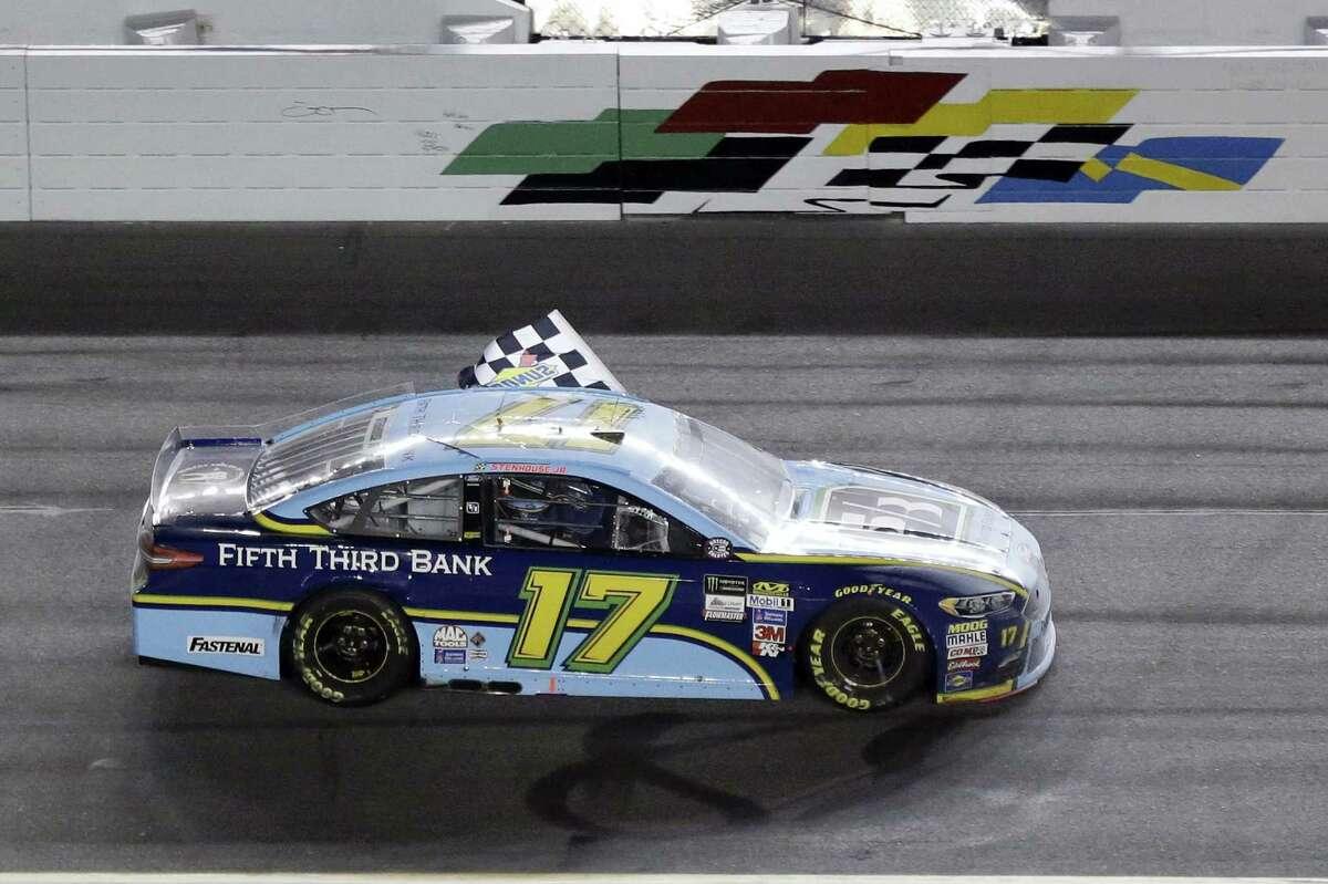 Ricky Stenhouse Jr. waves the checkered flag after winning at Daytona International Speedway on Saturday.