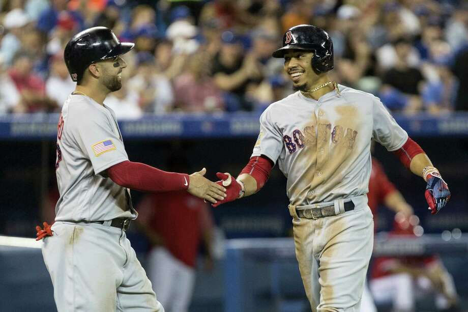 Mookie Betts, right, is congratulated by Deven Marrero as he crosses home plate after hitting a two-run home run in the sixth inning Sunday. Photo: Chris Young — The Canadian Press Via AP  / The Canadian Press