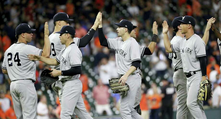 The  Yankees celebrate after the team's 13-4 win over the Astros on Friday. Photo: David J. Phillip — The Associated Press  / AP