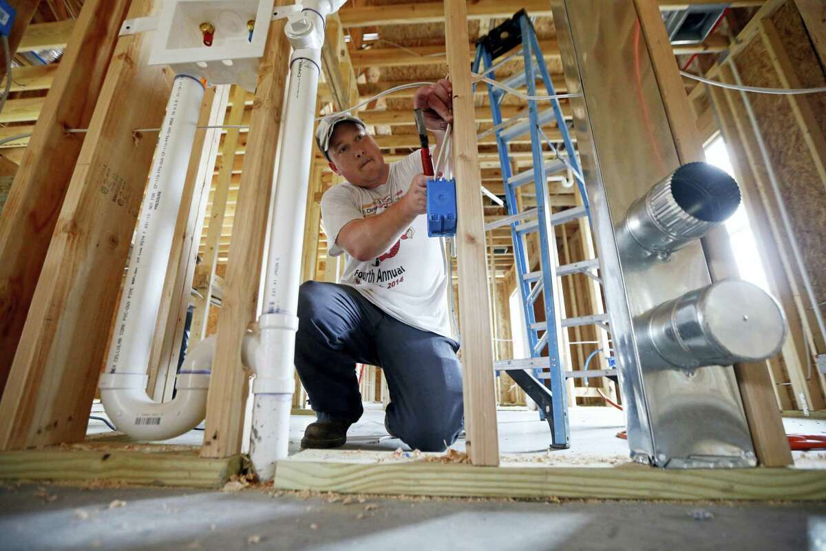 Chris Piazza, an electrician with Tasch Electric, works on a home being built by Zach Tyson of Tyson Construction, in Destrahan, La.