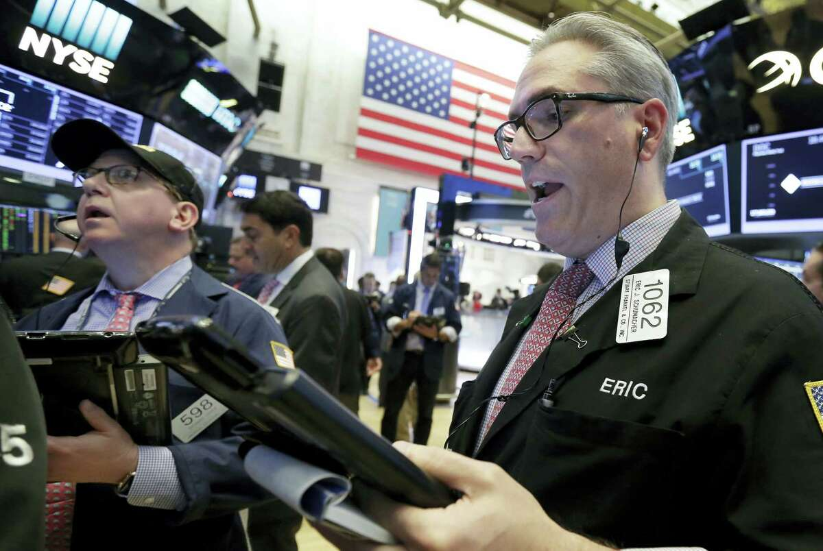 Traders Richard Cohen, left, and Eric Schumacher work on the floor of the New York Stock Exchange, Wednesday, Aug. 2, 2017. A big gain from Apple Wednesday morning sent the Dow Jones industrial average above 22,000 for the first time.