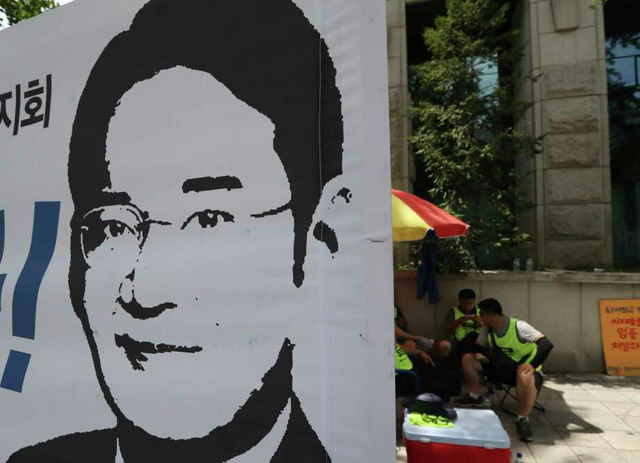 South Korean protesters sit near the banner with a picture of Lee Jae-yong, vice chairman of Samsung Electronics, near the Seoul Central District Court in Seoul, South Korea, Friday, Aug. 25, 2017. A court will rule Friday in a bribery case against the billionaire heir to the Samsung empire that fed public anger leading to the ouster of Park Geun-hye as South Korea's president. (AP Photo/Lee Jin-man) Photo: Lee Jin-man, STF / Copyright 2017 The Associated Press. All rights reserved.