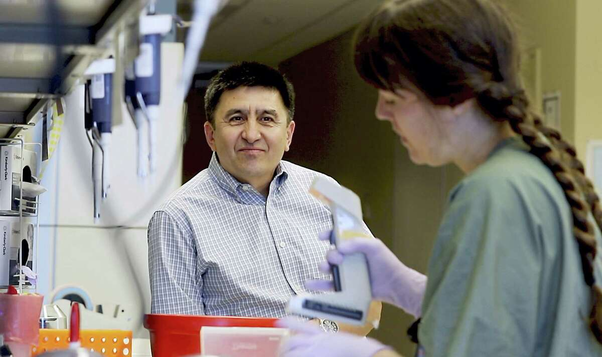 In this July 31, 2017, photo provided by Oregon Health & Science University, Shoukhrat Mitalipov, left, talks with research assistant Hayley Darby in the Mitalipov Lab at OHSU in Portland, Ore. Mitalipov led a research team that, for the first time, used gene editing to repair a disease-causing mutation in human embryos, laboratory experiments that might one day help prevent inherited diseases from being passed to future generations.