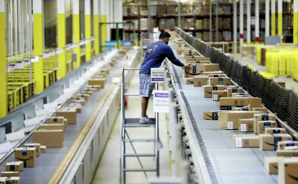 In this Aug. 1, 2017 photo, an Amazon employee makes sure a box riding on a belt is not sticking out at the Amazon Fulfillment center in Robbinsville Township, N.J. Amazon is holding a giant job fair Wednesday, Aug. 2, and plans to make thousands of job offers on the spot at nearly a dozen U.S. warehouses.