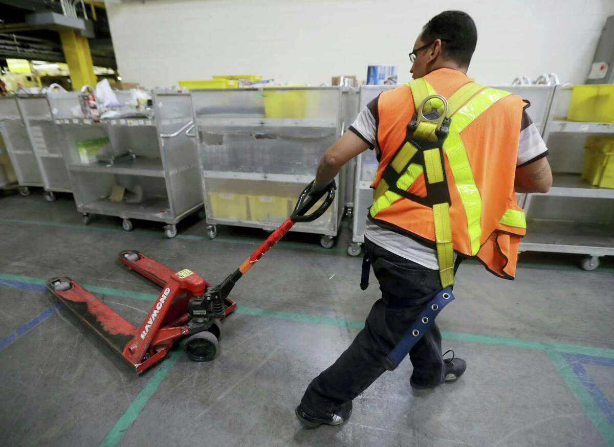 In this Aug. 1, 2017 photo, an Amazon employee pulls a dolly at the Amazon Fulfillment center in Robbinsville Township, N.J. Amazon is holding a giant job fair Wednesday, Aug. 2, and plans to make thousands of job offers on the spot at nearly a dozen U.S. warehouses.