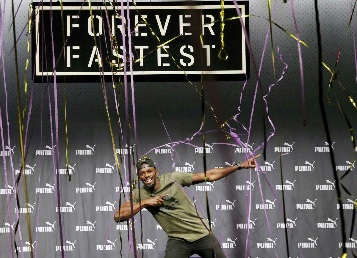 Usain Bolt celebrates after a press conference ahead of the World Athletics championships in London on Tuesday.