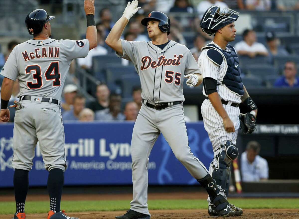 The Tigers' James McCann (34) greets John Hicks at the plate after Hicks' three-run home run in the second inning on Tuesday.