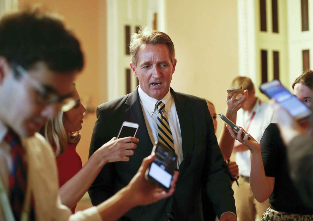 """In this July 13, 2017, file photo, Sen. Jeff Flake, R-Ariz. speaks to members of the media as he walks to a meeting on Capitol Hill in Washington. There wasn't a dramatic public break, or a precise moment when it happened. But little by little, Senate Republicans have been turning their backs on President Donald Trump. They've defied his Twitter demands, defeated his top agenda item and passed veto-proof sanctions on Russia over administration objections. Flake took aim at Trump and his own party in a new book, writing that """"Unnerving silence in the face of an erratic executive branch is an abdication"""" and """"the strange specter of an American president's seeming affection for strongmen and authoritarians created such a cognitive dissonance among my generation of conservatives — who had come of age under existential threat from the Soviet Union — that it was almost impossible to believe."""""""