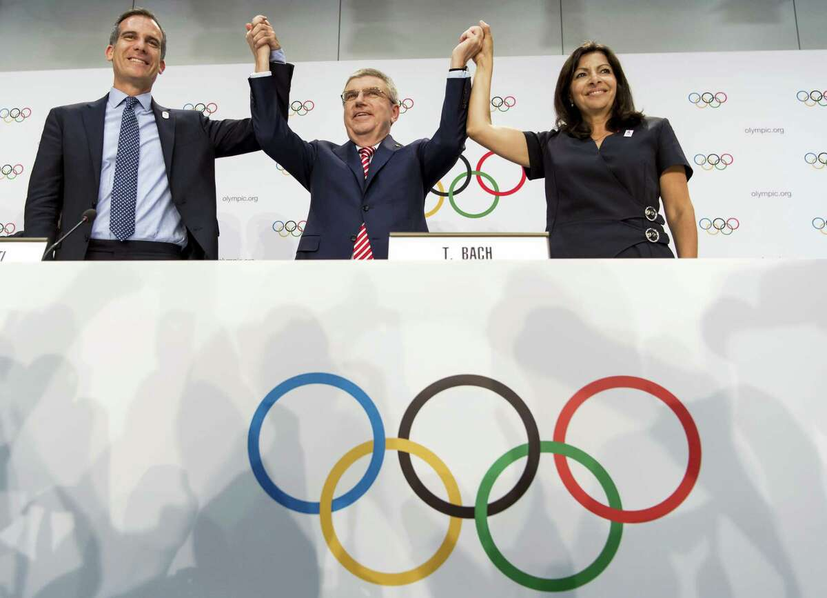 FILE - Int his July 11, 2017, file photo, from left, Mayor of Los Angeles Eric Garcetti, International Olympic Committee (IOC) President Thomas Bach, and Mayor of Paris Anne Hidalgo gesture during a press conference after the IOC Extraordinary Session at the SwissTech Convention Centre in Lausanne, Switzerland. One of the beautiful things about the Olympics is that some of the runners-up get prizes, too. Which brings us to Los Angeles.