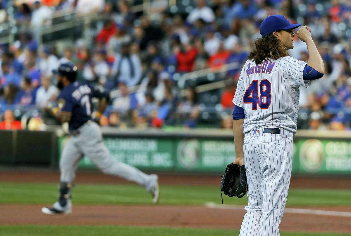 New York Mets pitcher Jacob deGrom (48) reacts after giving up a two-run home run to Milwaukee Brewers' Eric Thames (7) during the first inning Wednesday in New York.