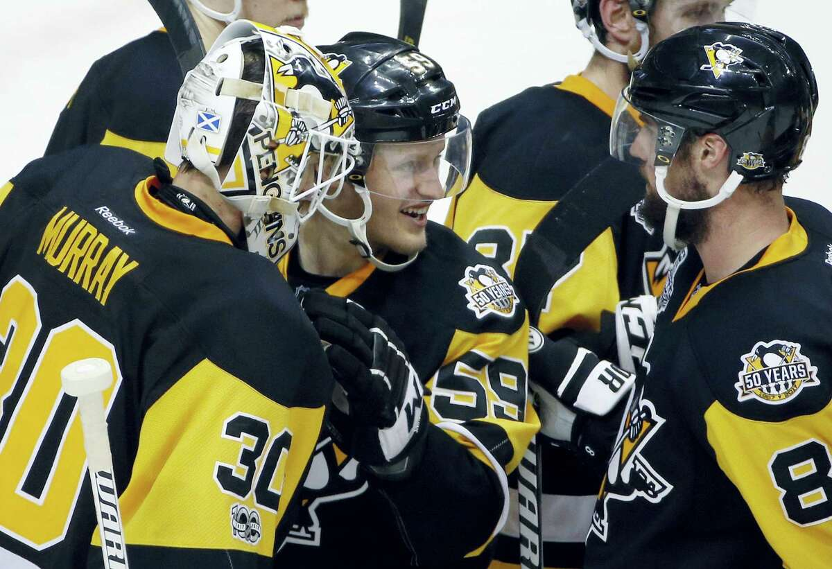 Pittsburgh Penguins' Matt Murray, left, Jake Guentzel, center, and Brian Dumoulin celebrate after the Penguins defeated the Nashville Predators 4-1 in Game 2 of the Stanley Cup Final, Wednesday in Pittsburgh.