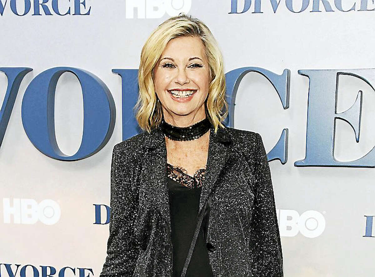 """In this Oct. 4, 2016, file photo, actress and singer Olivia Newton-John attends the premiere of HBO's """"Divorce"""" in New York. Newton-John says she has breast cancer and is canceling her June tour. The 68-year-old singer announced Tuesday, May 30, 2017, that she initially thought she was suffering from back pain, but learned it was """"breast cancer that has metastasized to the sacrum."""""""