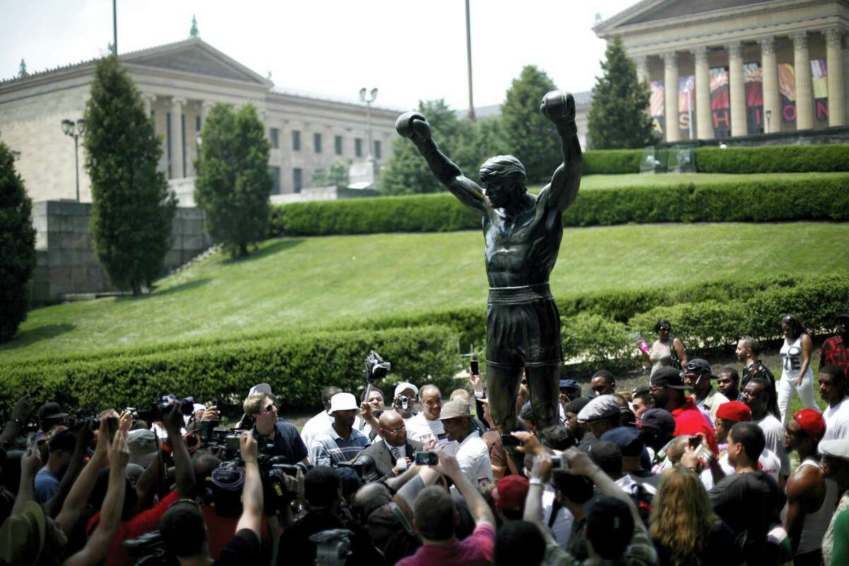 In a Wednesday, June 1, 2011, file photo, boxer Bernard Hopkins, center, and Mayor Michael Nutter, center left, pose for photographs at the base of the Rocky statue in Philadelphia. On Tuesday, May 30, 2017, the city's Department of Parks and Recreation said the statue will be closed to tourists for two weeks while improvements are being made to the site surrounding the statue at the head of the Benjamin Franklin Parkway.