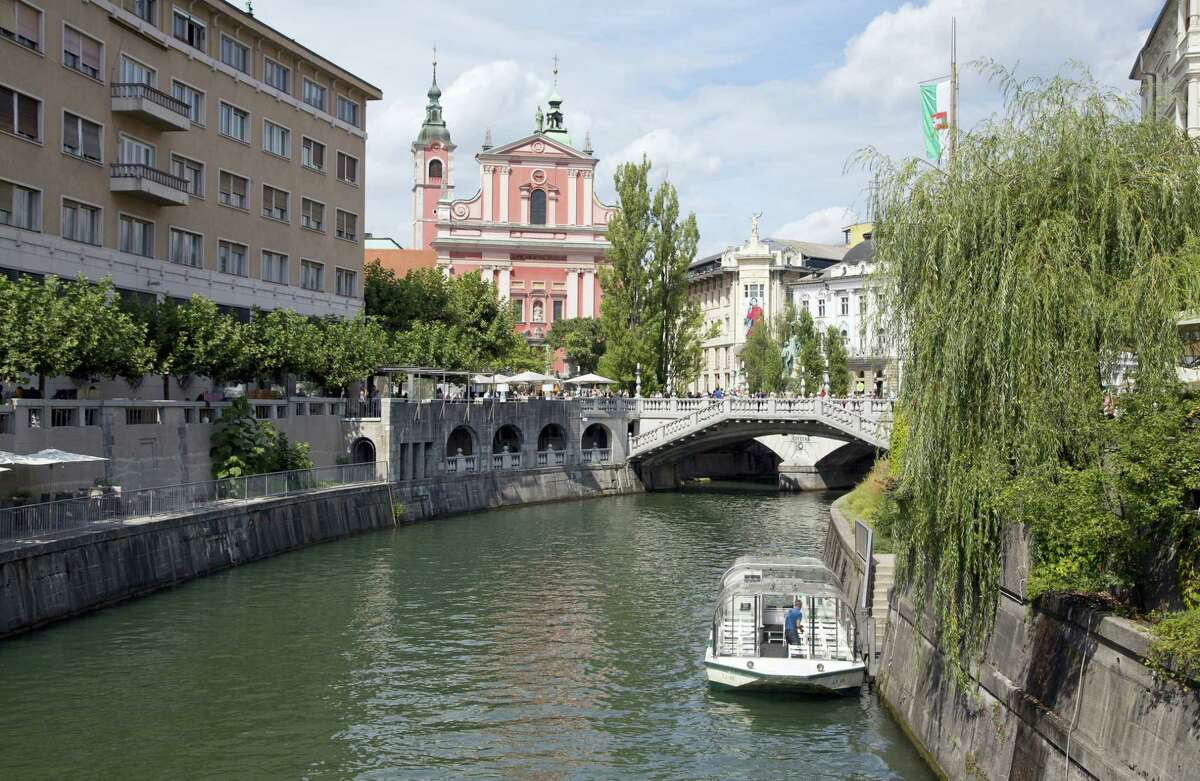 In this Friday, Aug. 12, 2016, file photo, tourists and residents walk across Tromostovje bridges in downtown Ljubljana, Slovenia. The tiny European nation of Slovenia is undergoing a tourism boom partly because it is the native country of U.S. first lady Melania Trump.