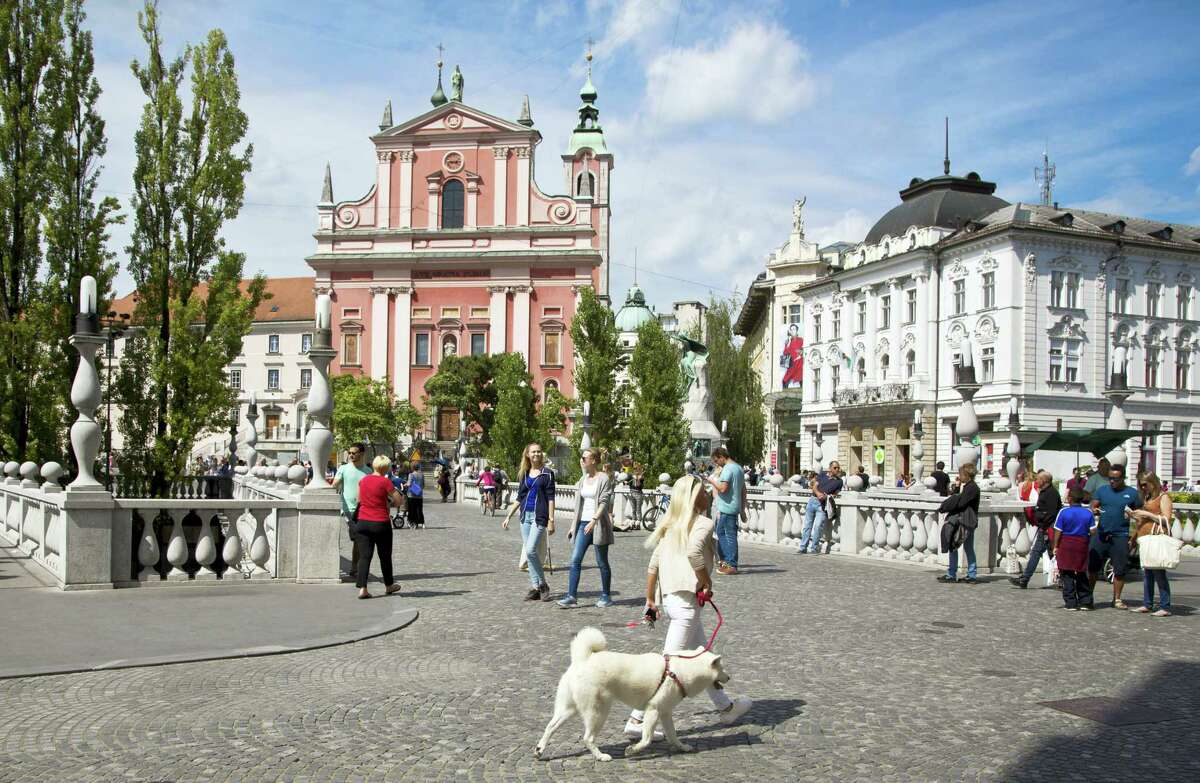 In this Friday, Aug. 12, 2016, file photo, tourists and residents walk across Tromostovje bridge in downtown Ljubljana, Slovenia The tiny European nation of Slovenia is undergoing a tourism boom partly because it is the native country of U.S. first lady Melania Trump.