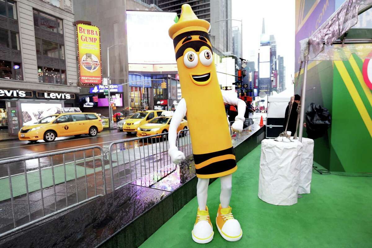 """A dandelion crayon character poses for photos during a Crayola event in New York's Times Square, Friday, March 31, 2017. Crayola announced Friday, National Crayon Day, that it's replacing the color dandelion in its 24-pack with a crayon in """"the blue family."""""""