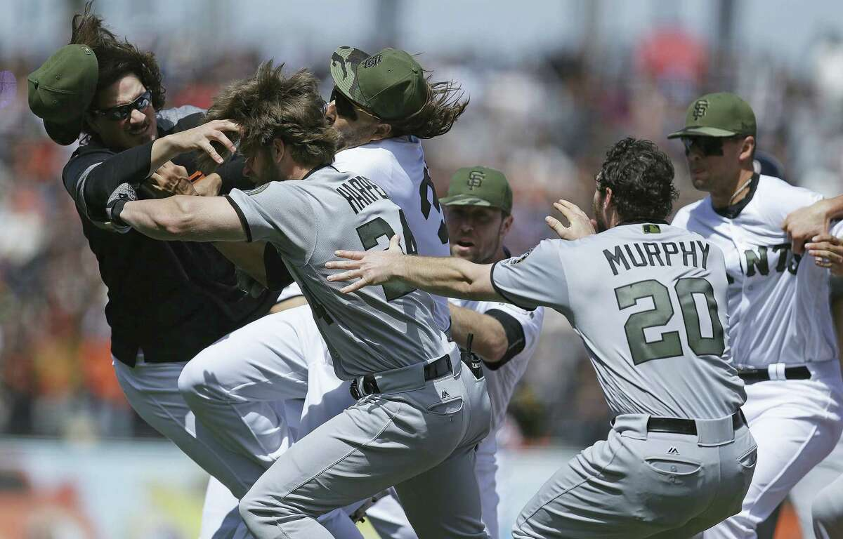 Washington Nationals' Daniel Murphy (20) tries to restrain teammate Bryce Harper (34) after Harper charged San Francisco Giants' Hunter Strickland after being hit with a pitch in the eighth inning of a baseball game Monday, May 29, 2017 in San Francisco.