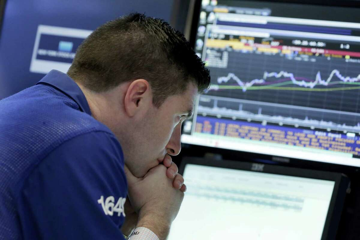 Specialist Thomas McArdle works at his post on the floor of the New York Stock Exchange Thursday.