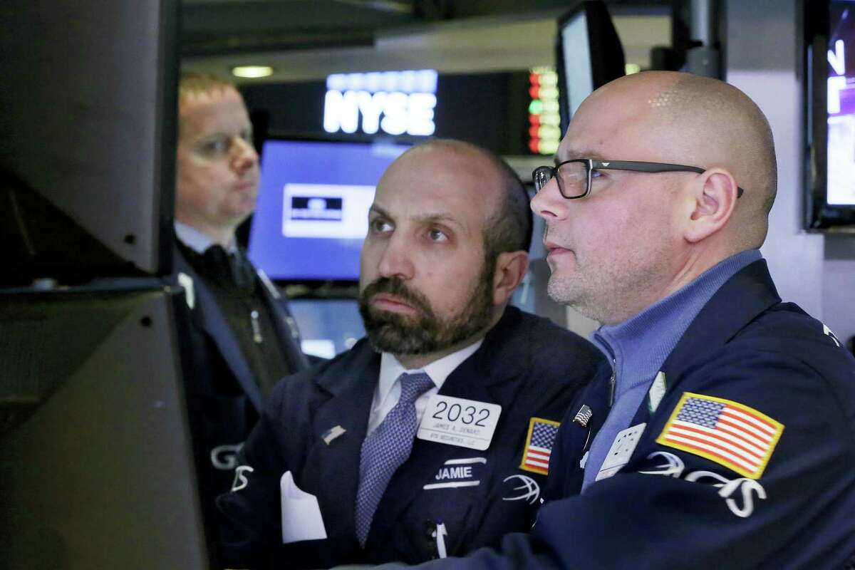 Specialists Mario Picone, right, and James Denaro, center, work on the floor of the New York Stock Exchange Thursday.