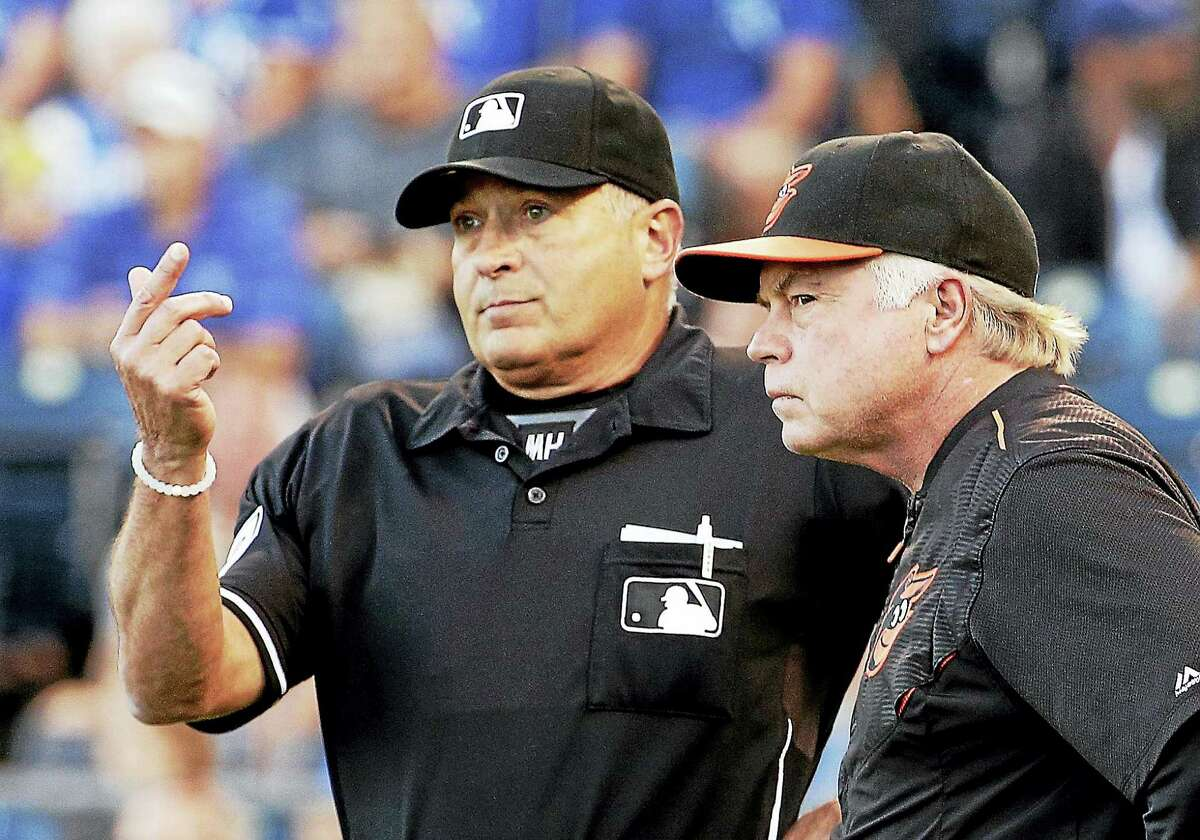 Home plate umpire John Hirschbeck calls for assistance from a fellow umpire after Baltimore Orioles manager Buck Showalter questioned a call during the first inning of a baseball game against the Kansas City Royals Monday, Aug. 24, 2015, in Kansas City, Mo. (AP Photo/Charlie Riedel)