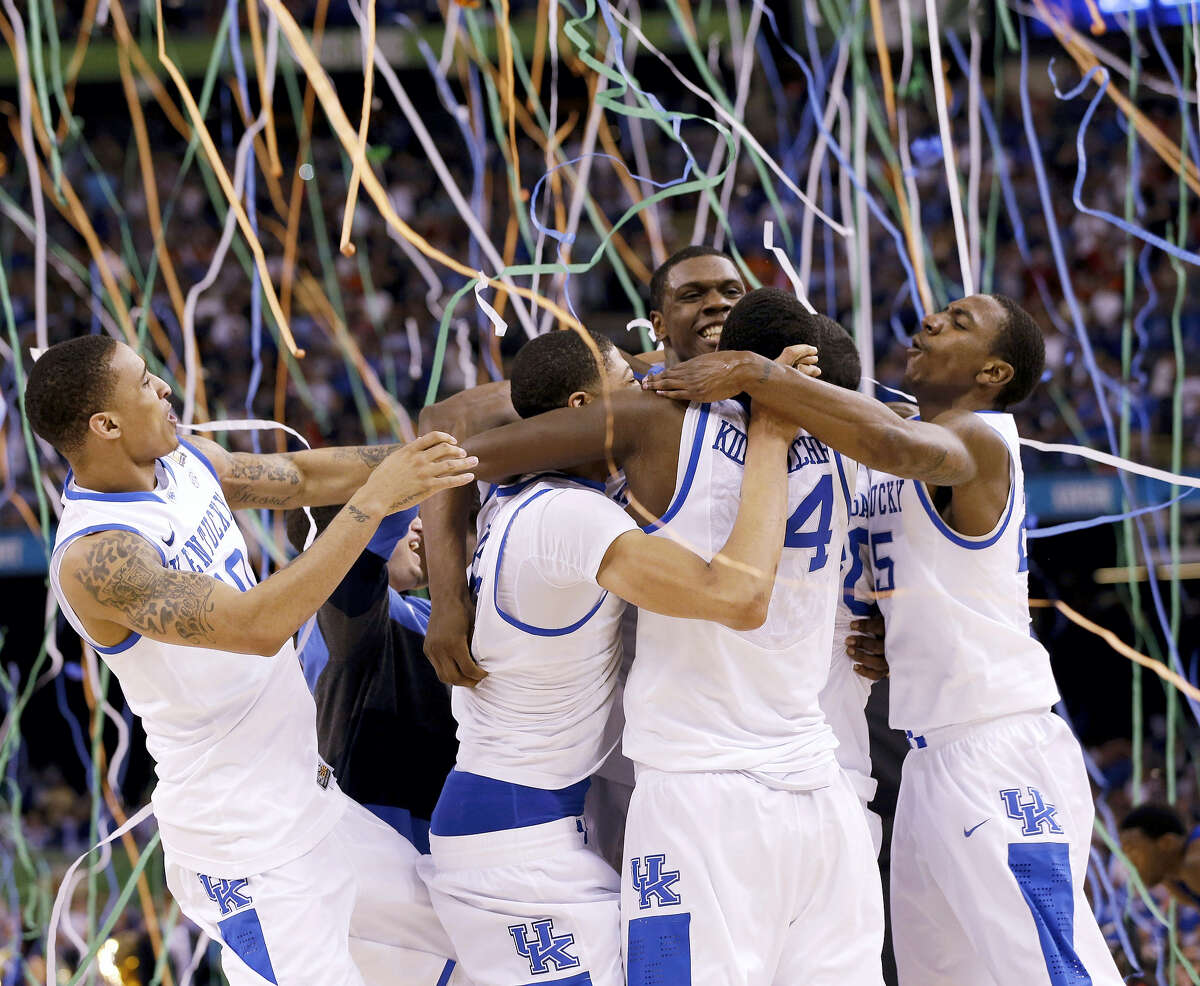 In this April 2, 2012, file photo, Kentucky players celebrate ITS NATIONAL CHAMPIONSHIP against Kansas. The Associated Press is ranking the top 100 college basketball programs of all time using 68 years of data from the AP Top 25 poll.