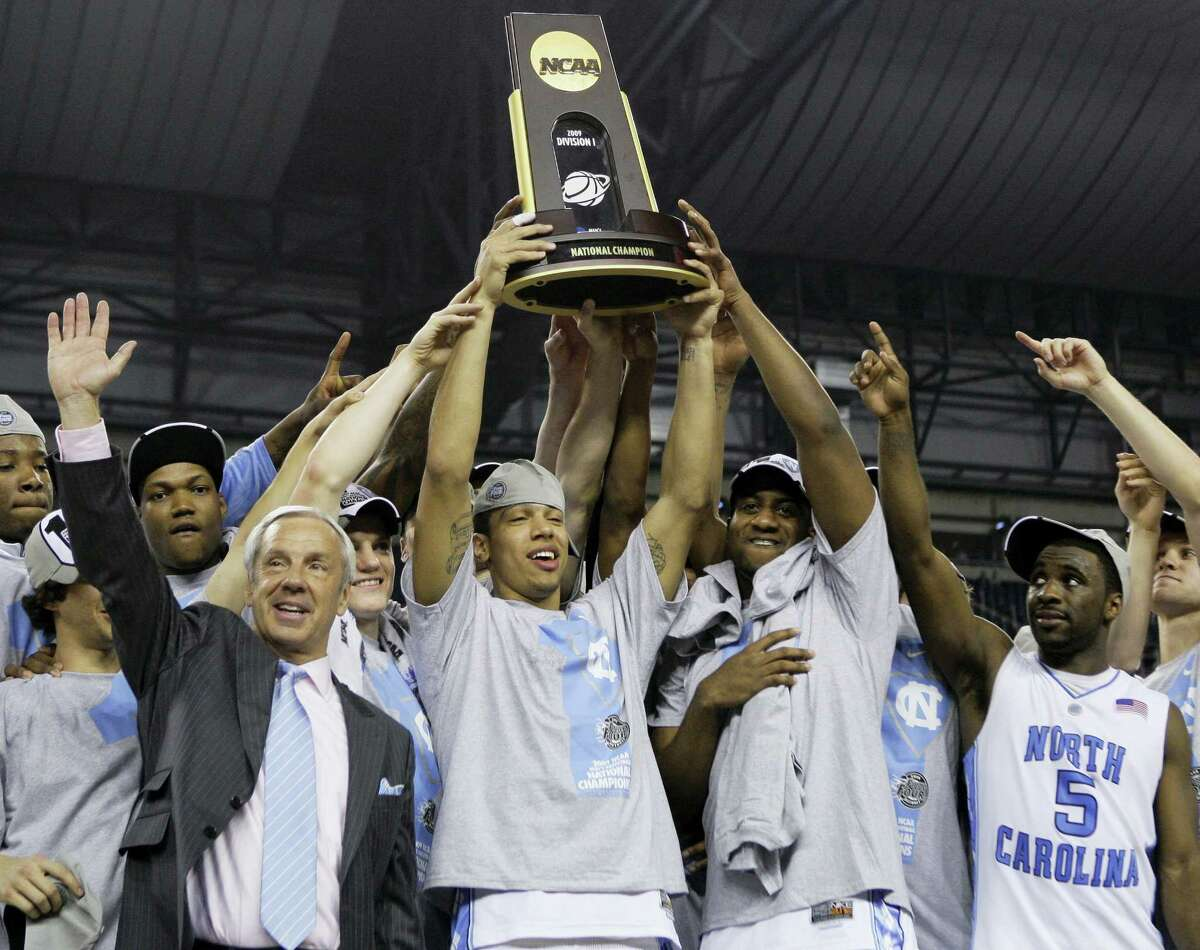 In this April 6, 2009, file photo, North Carolina head coach Roy Williams and players hold the trophy after their 89-72 win over Michigan State in the championship game at the men's NCAA Final Four in Detroit.