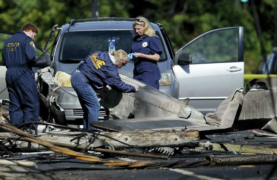 In this file photo, investigators look at the remains of a small plane along Main Street in East Hartford, Conn. Police say the student pilot of the small plane, which crashed on Oct. 11, near the Connecticut headquarters of a military jet engine manufacturer, fought with his instructor and probably crashed deliberately. East Hartford police reports disclosed Tuesday support media stories from months ago. Photo: Jessica Hill — The Associated Press File  / FR125654 AP